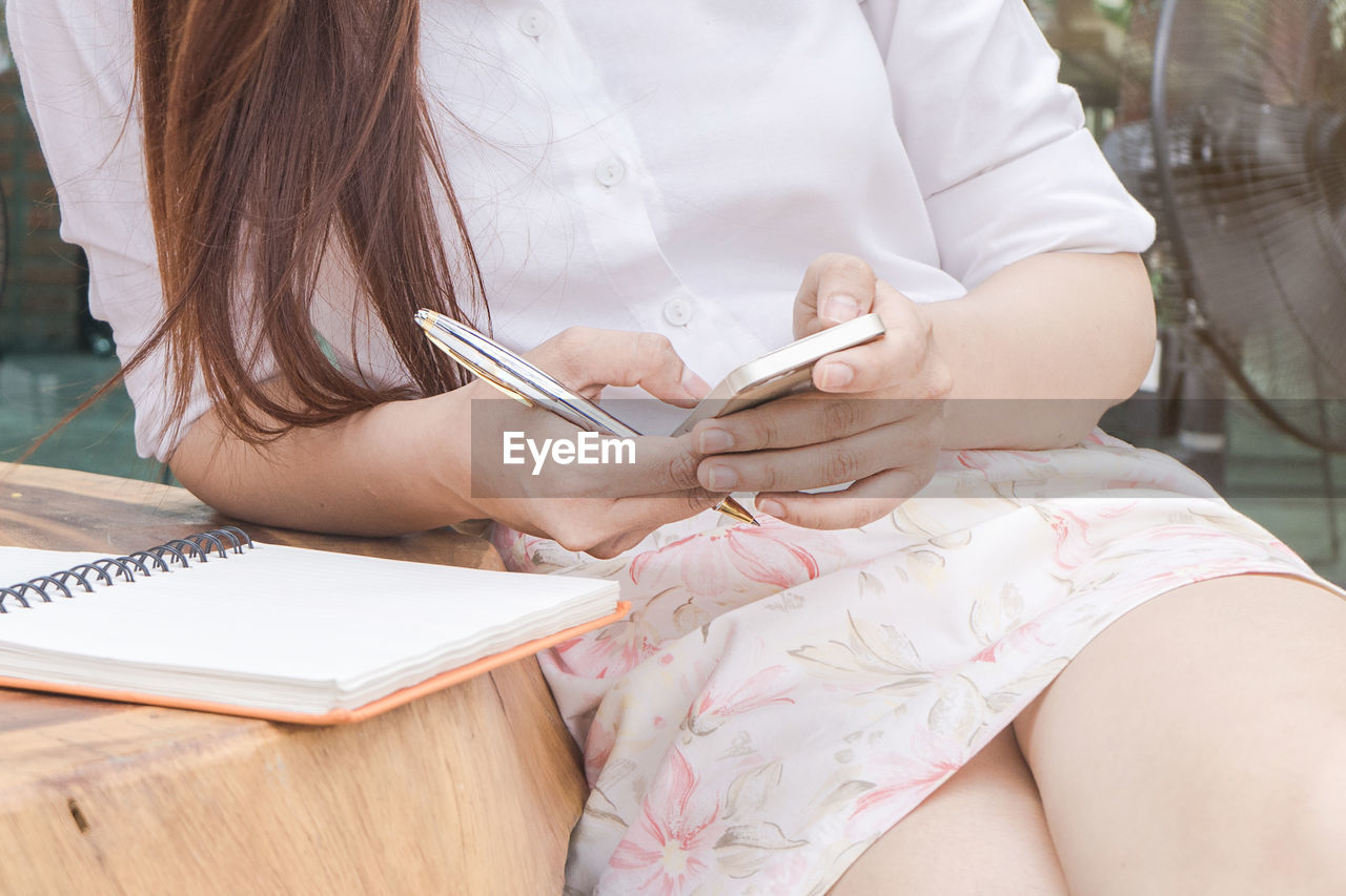 Midsection of young woman using mobile phone while sitting at table