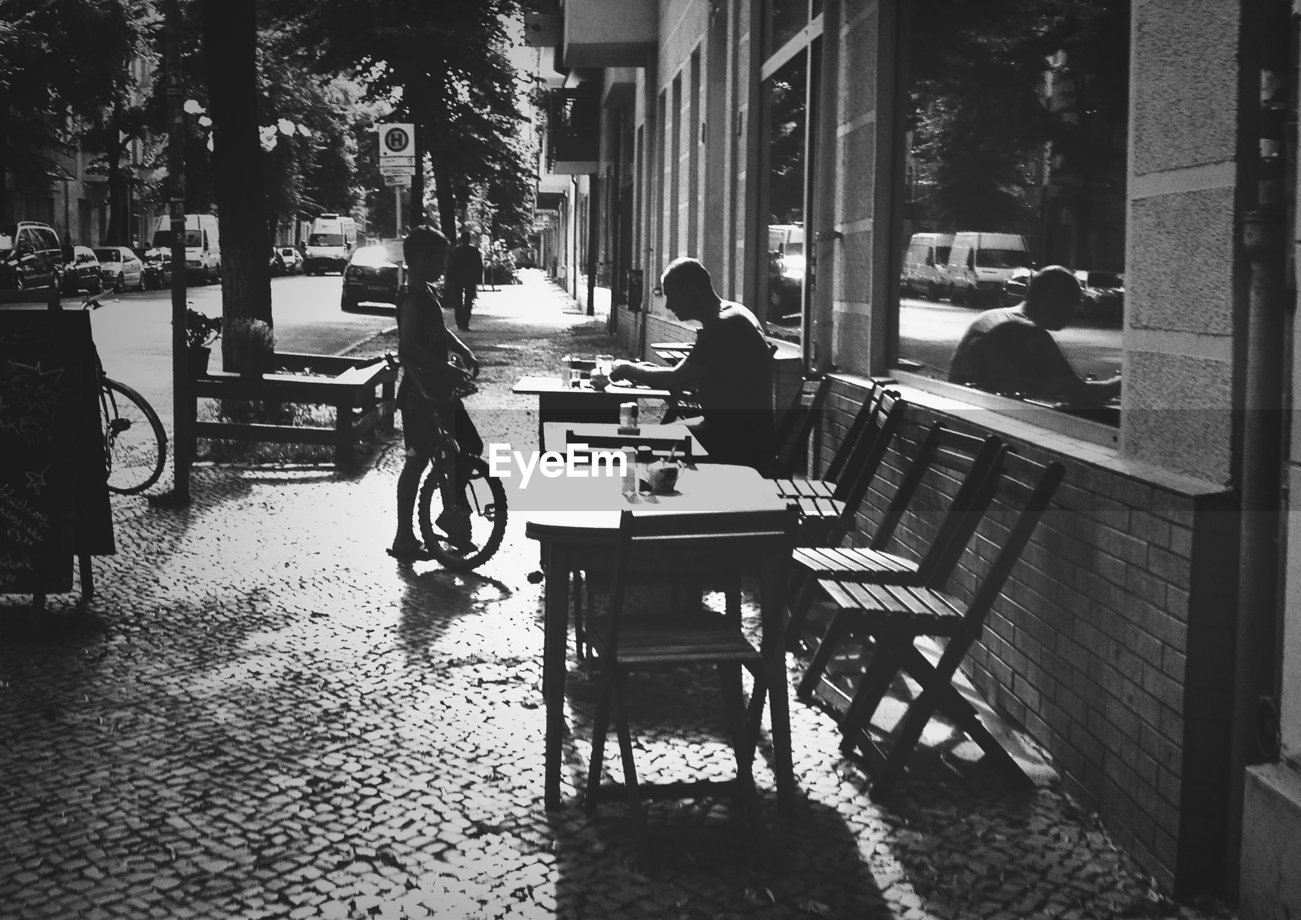 building exterior, architecture, built structure, chair, city, table, sitting, incidental people, sidewalk cafe, street, bench, city life, day, car, sunlight, men, mode of transport, transportation, relaxation