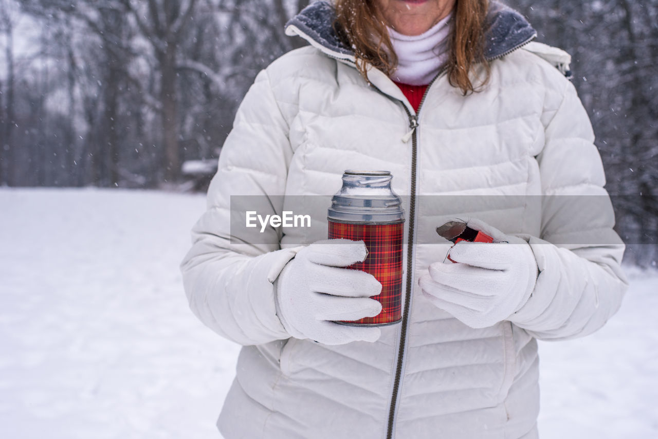 Midsection of woman holding bottle standing in snow
