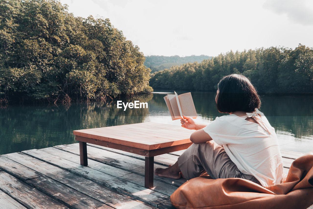 MAN SITTING BY TREE AGAINST LAKE