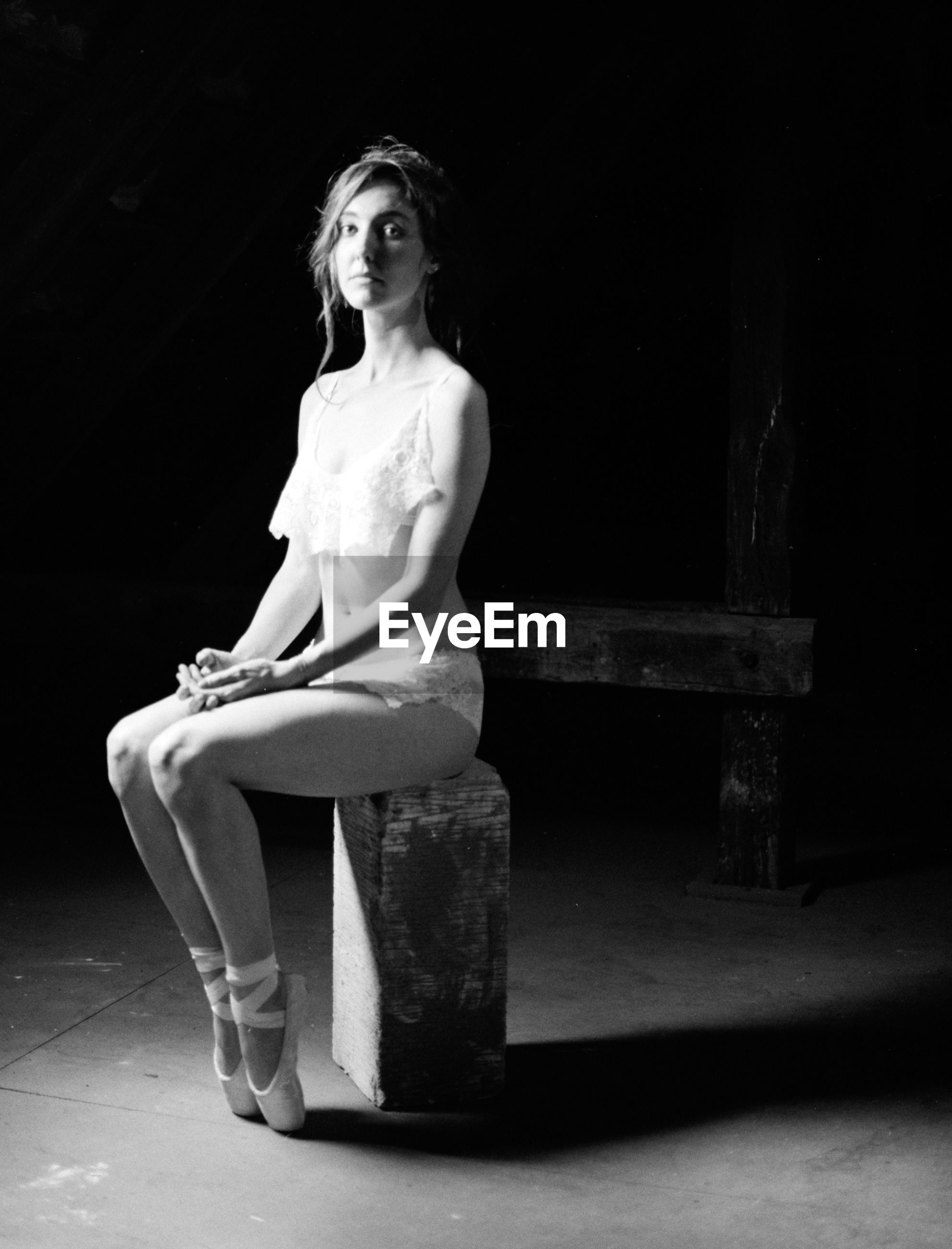 Full length of ballet dancer sitting on wood at night