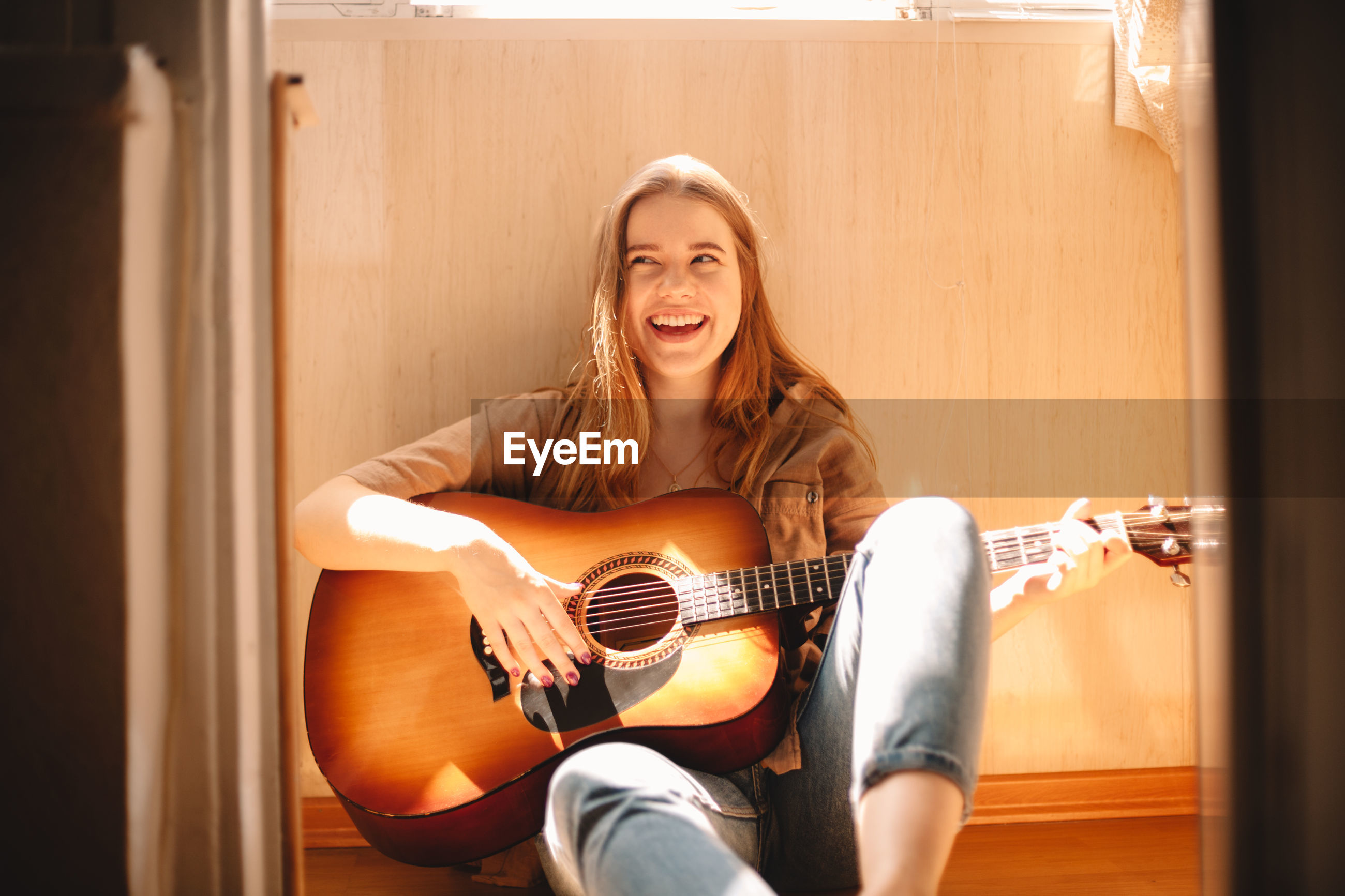 PORTRAIT OF A SMILING YOUNG WOMAN PLAYING GUITAR IN THE ROOM