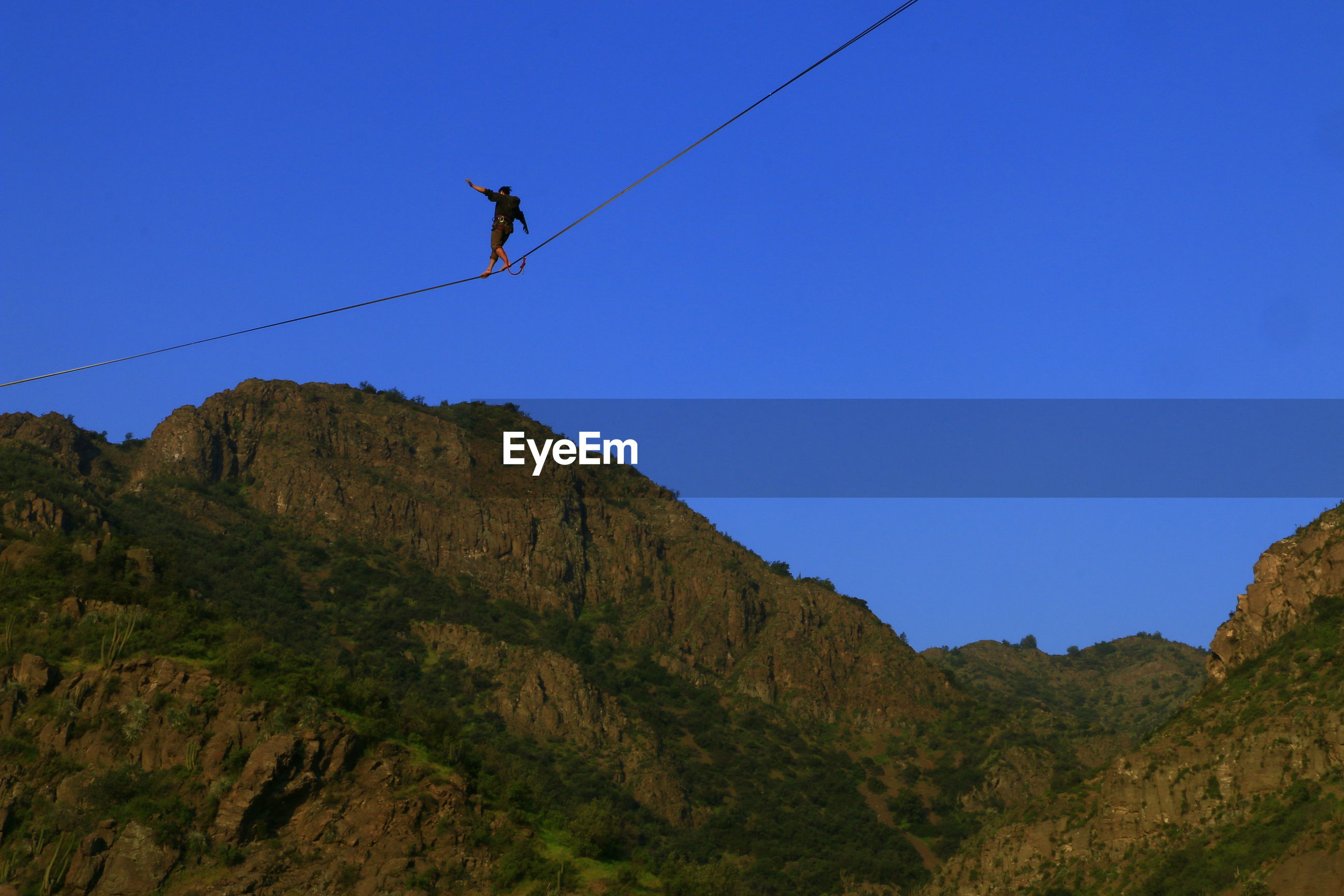 Low angle view of man walking on slackline over mountains against clear sky