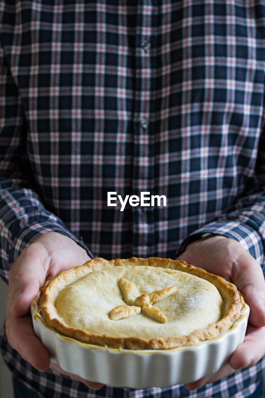 Close-Up Of Hand Holding Pie