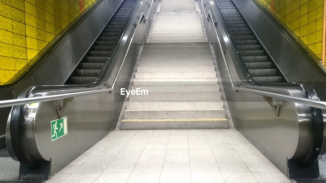 Low angle view of steps amidst escalators in subway