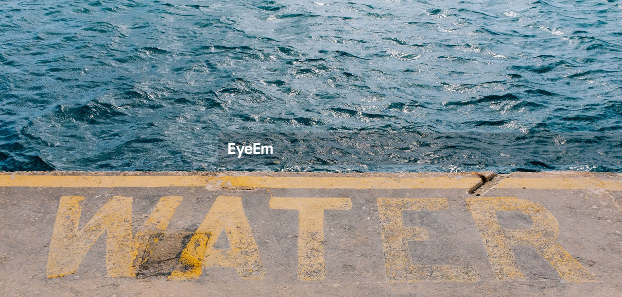 High Angle View Of Text On Pier In Sea