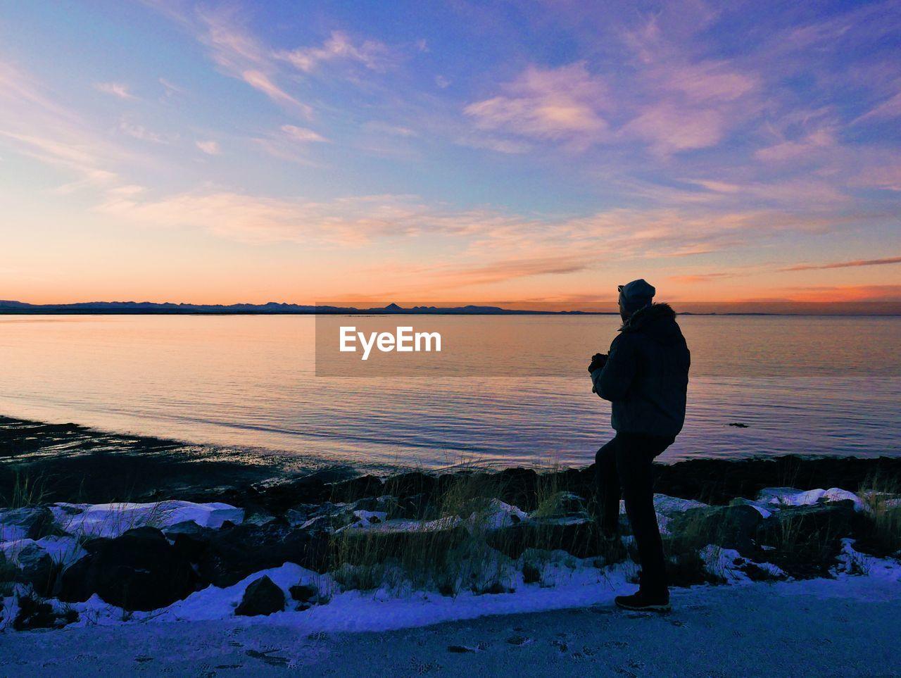 MAN STANDING ON SHORE AGAINST SUNSET SKY