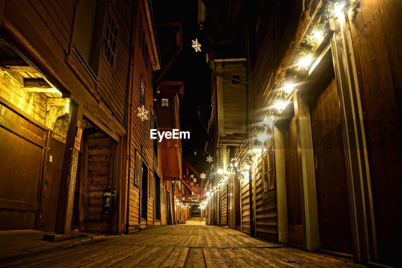 Narrow Pathway Amidst Illuminated Wooden Houses