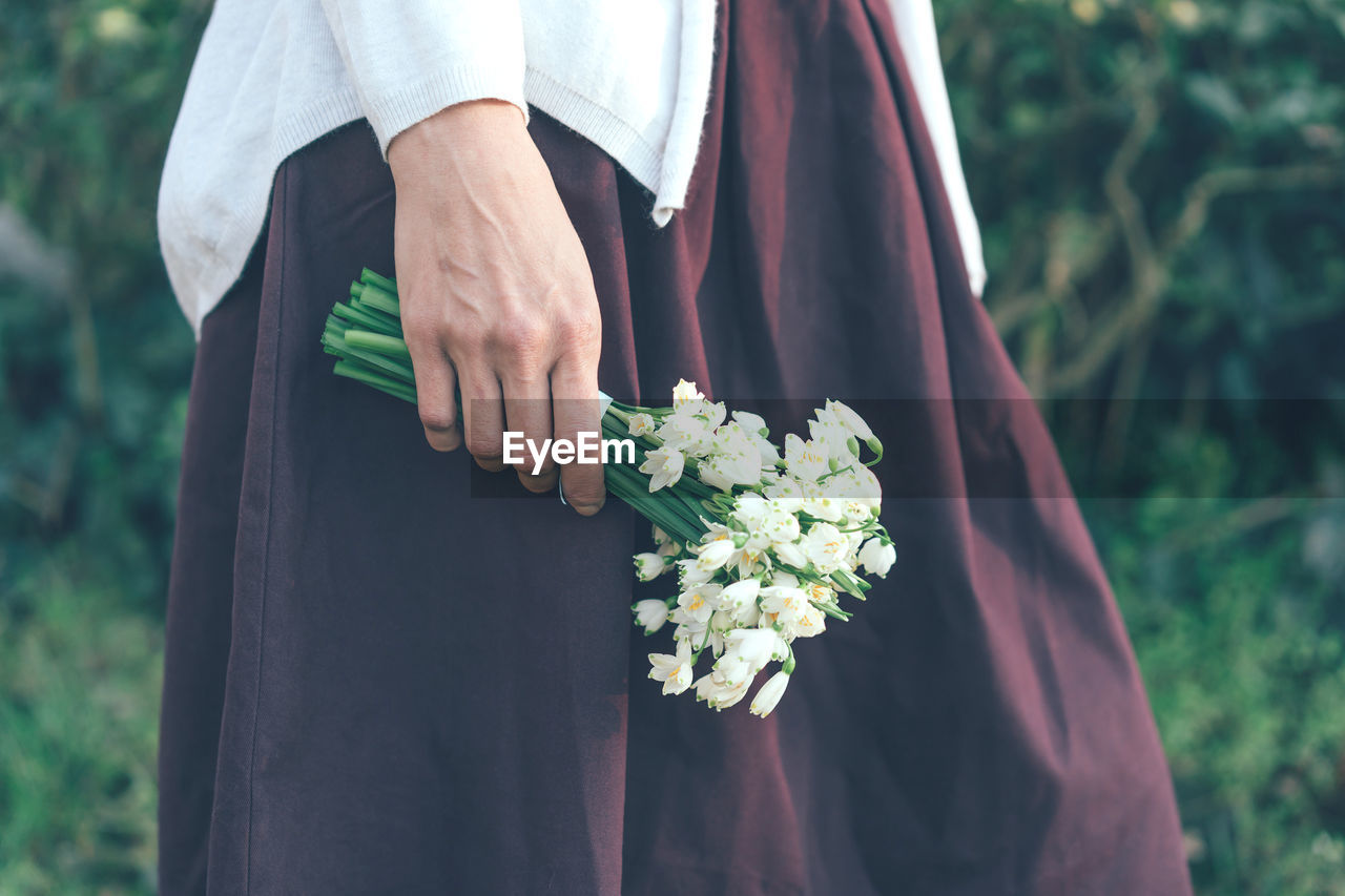 MIDSECTION OF MAN HOLDING FLOWER BOUQUET AGAINST PLANTS