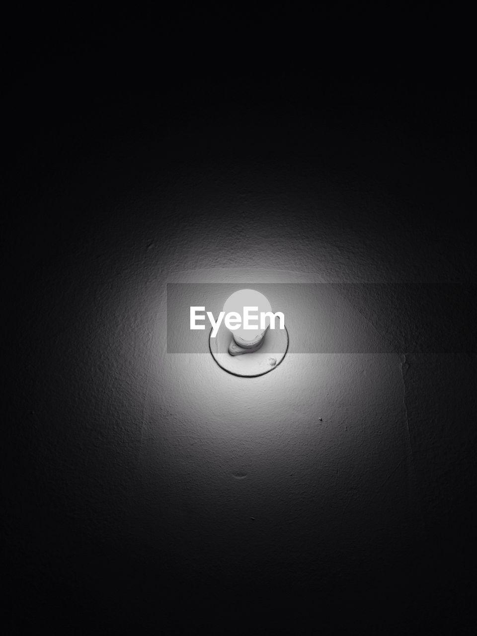 Illuminated electric bulb on wall