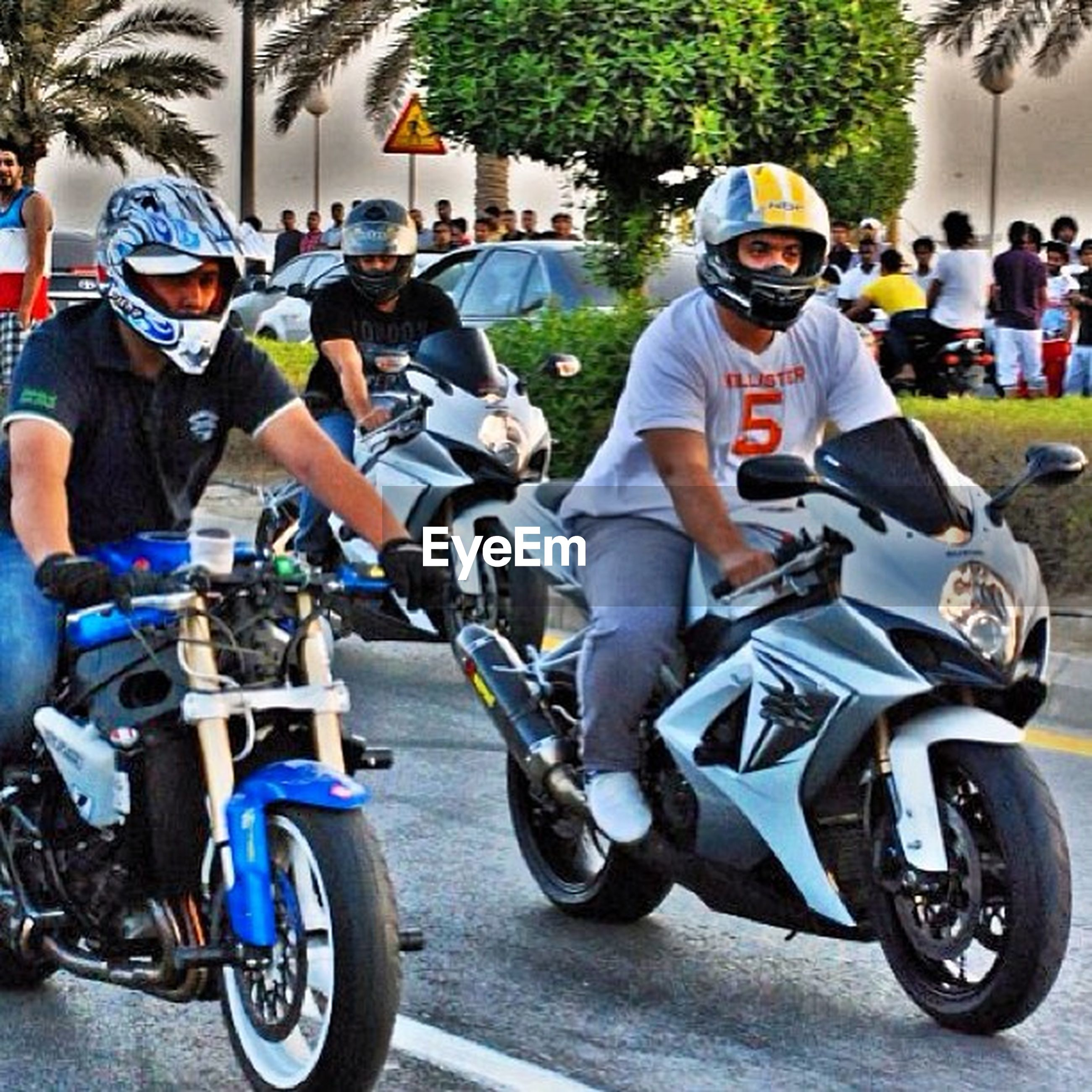 lifestyles, land vehicle, leisure activity, bicycle, men, transportation, mode of transport, casual clothing, riding, motorcycle, togetherness, street, full length, sitting, large group of people, person, boys, helmet, day