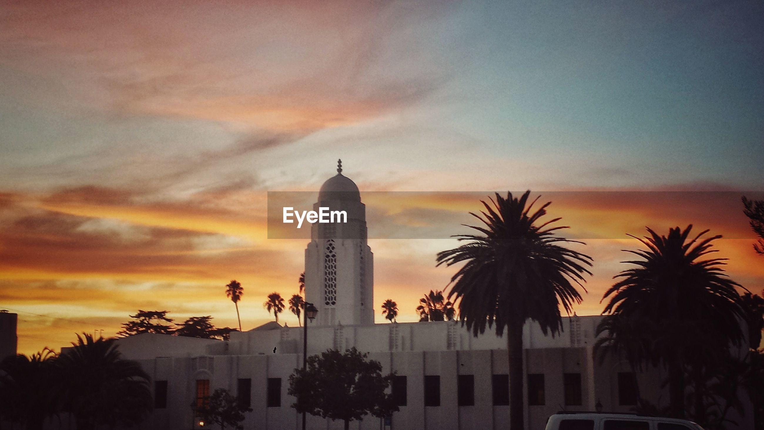 sunset, architecture, palm tree, building exterior, built structure, sky, tall - high, orange color, low angle view, city, silhouette, tower, skyscraper, modern, cloud - sky, tree, office building, cloud, growth, building