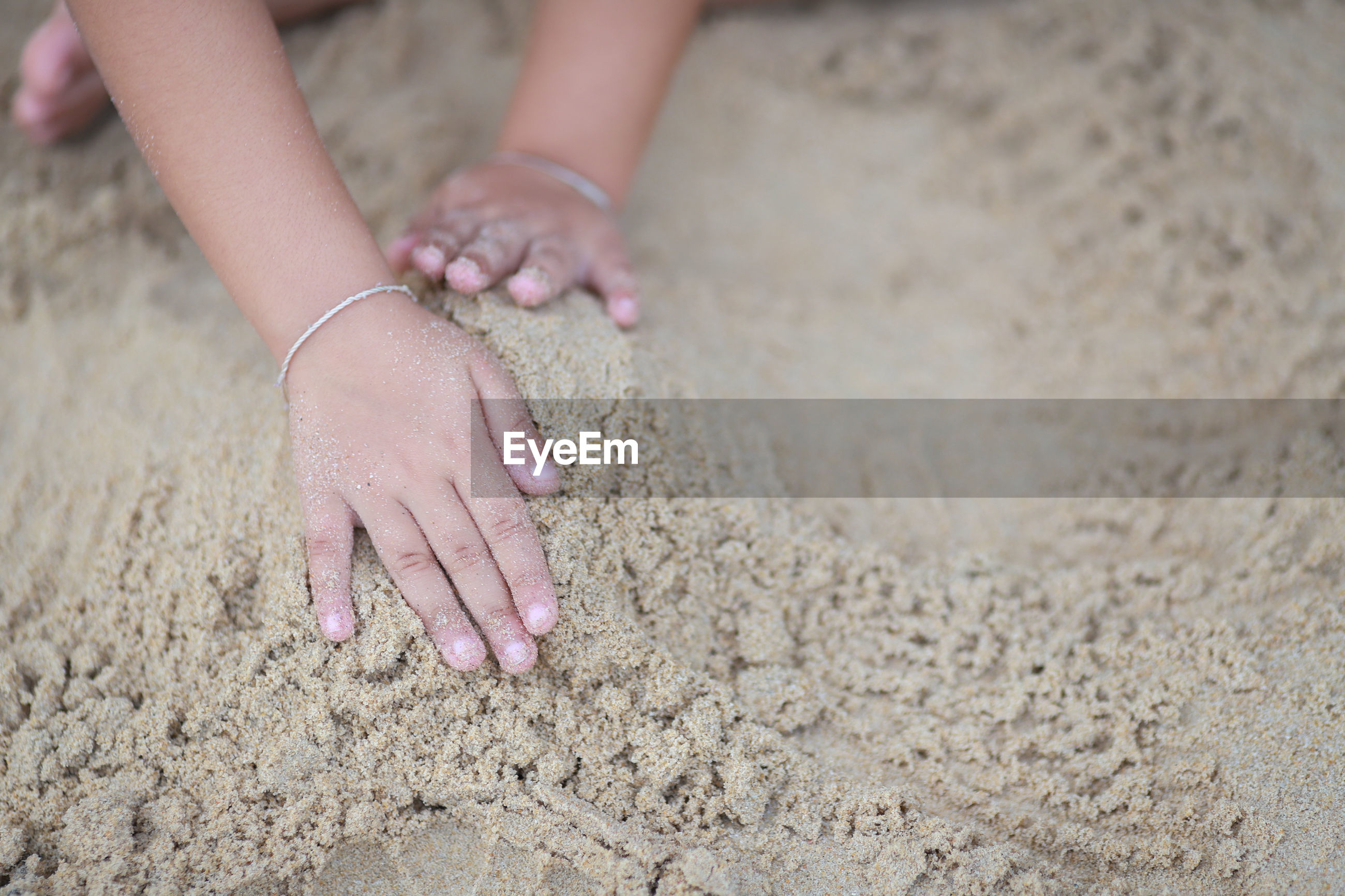 Close-up of child playing on sand