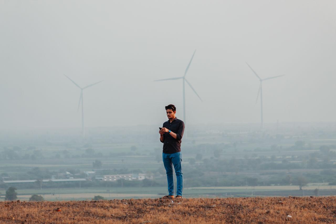 Man standing on hills against windmills