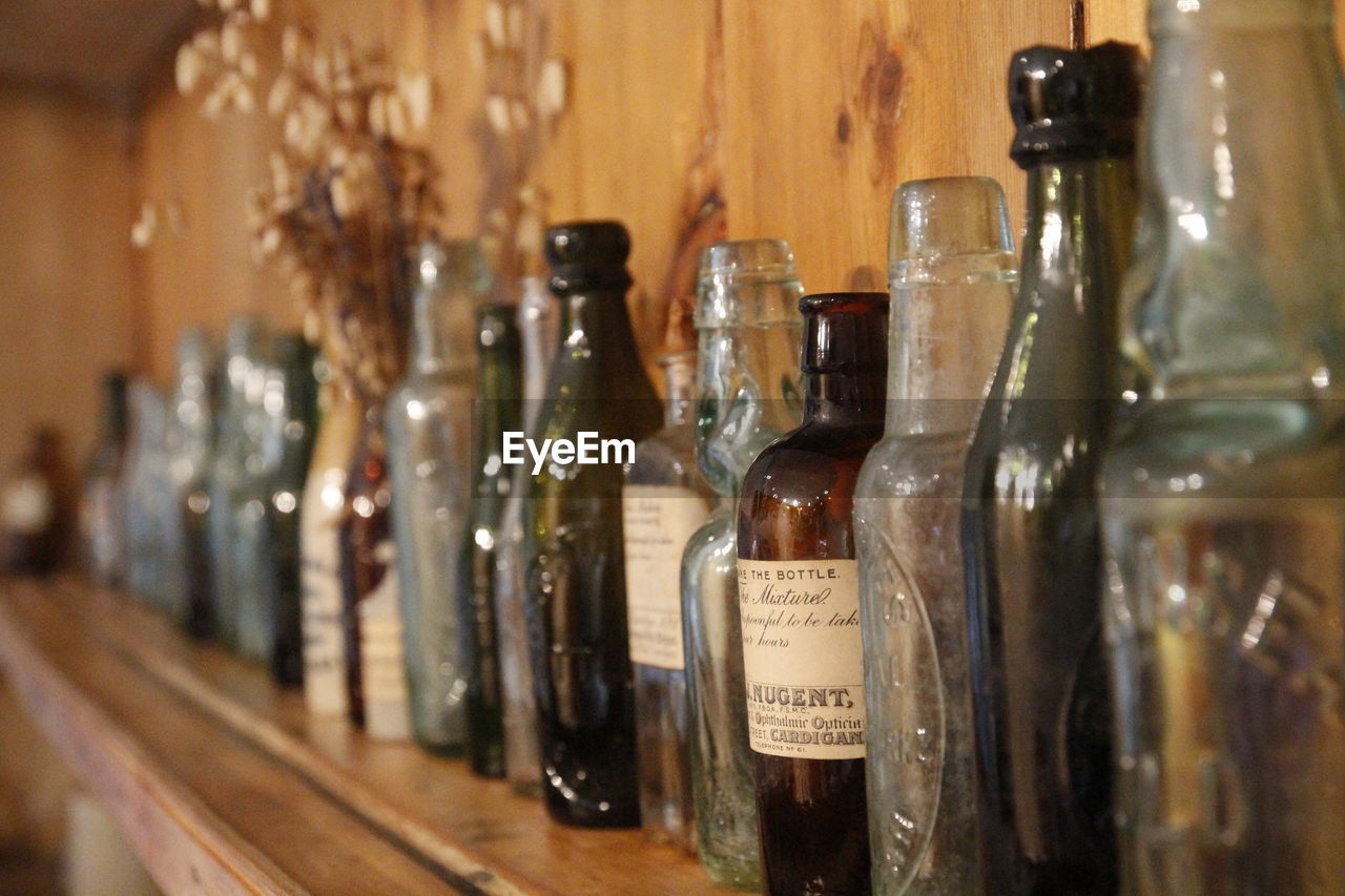 bottle, container, indoors, glass - material, alcohol, wine bottle, transparent, variation, choice, in a row, drink, still life, no people, refreshment, food and drink, close-up, focus on foreground, shelf, arrangement, wine