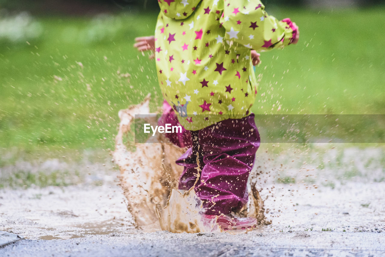 Low Section Of Child Playing In Puddle