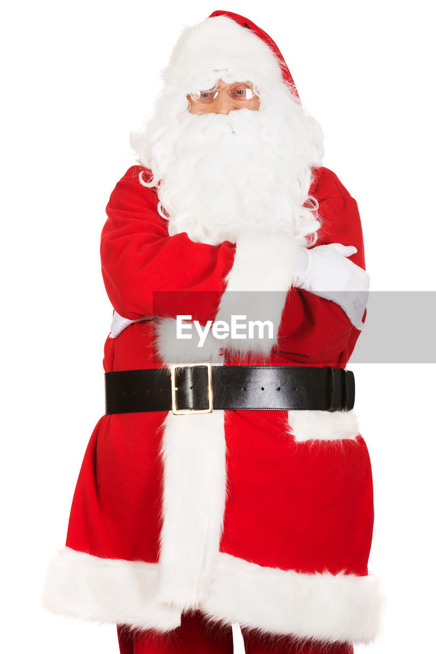 Portrait of man standing in santa claus costume against white background