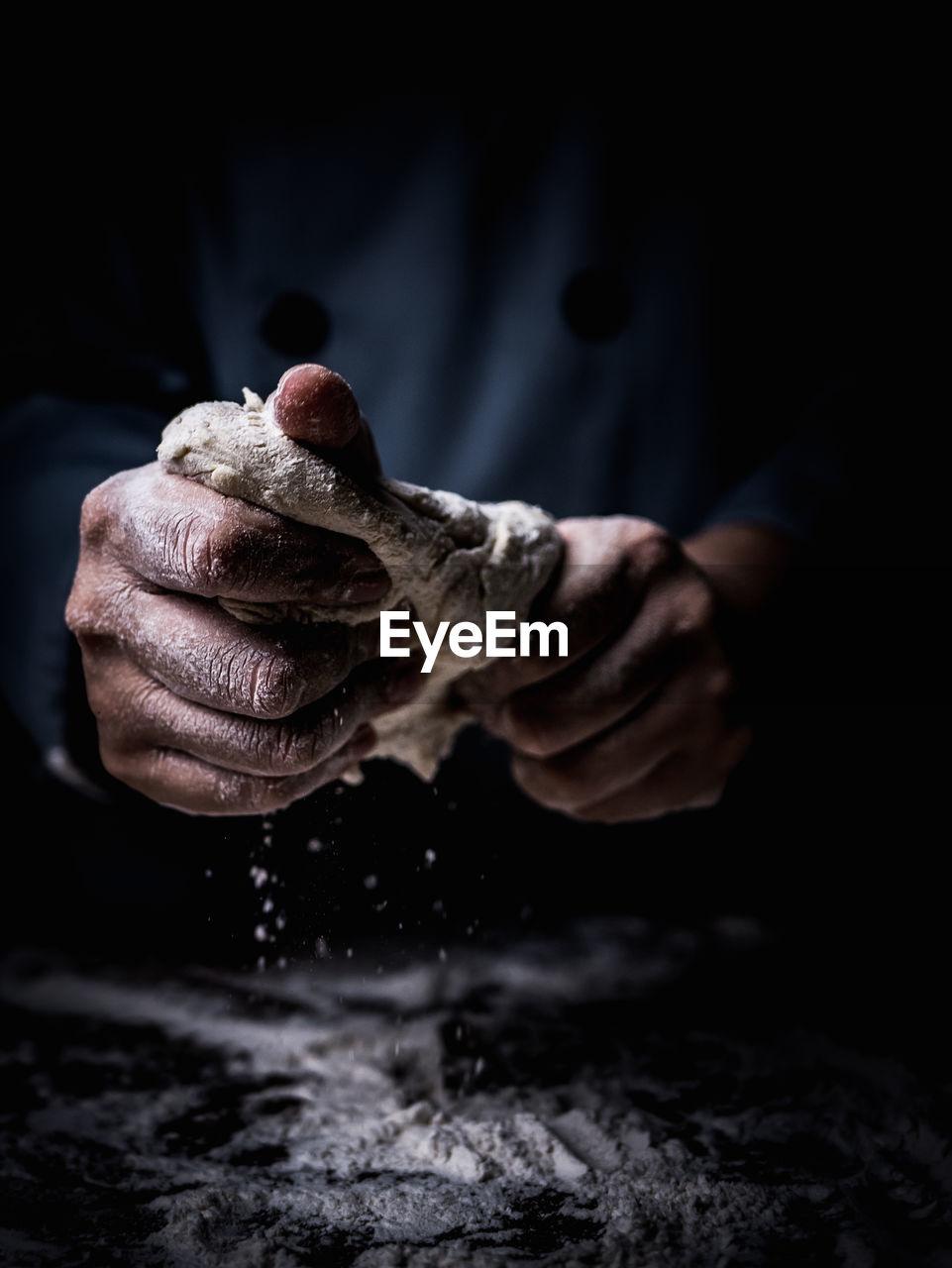 Close-up of man kneading dough