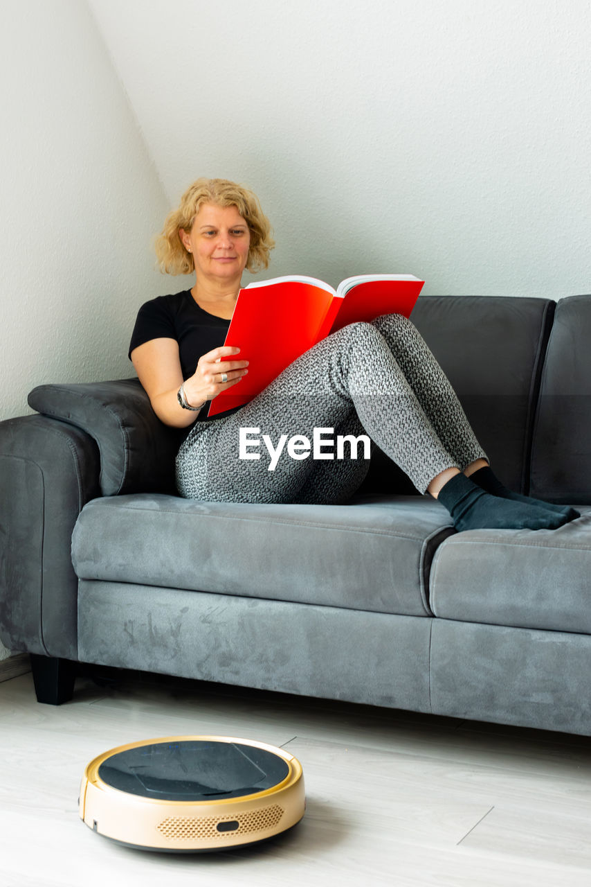 Woman reading book while sitting on sofa at home by vacuum cleaner
