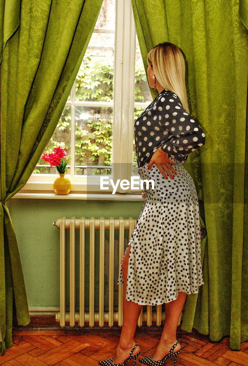 Woman looking through window while standing at home