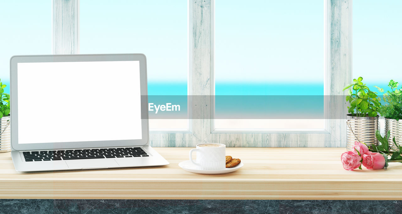 Close-Up Of Laptop And Breakfast On Table By Window