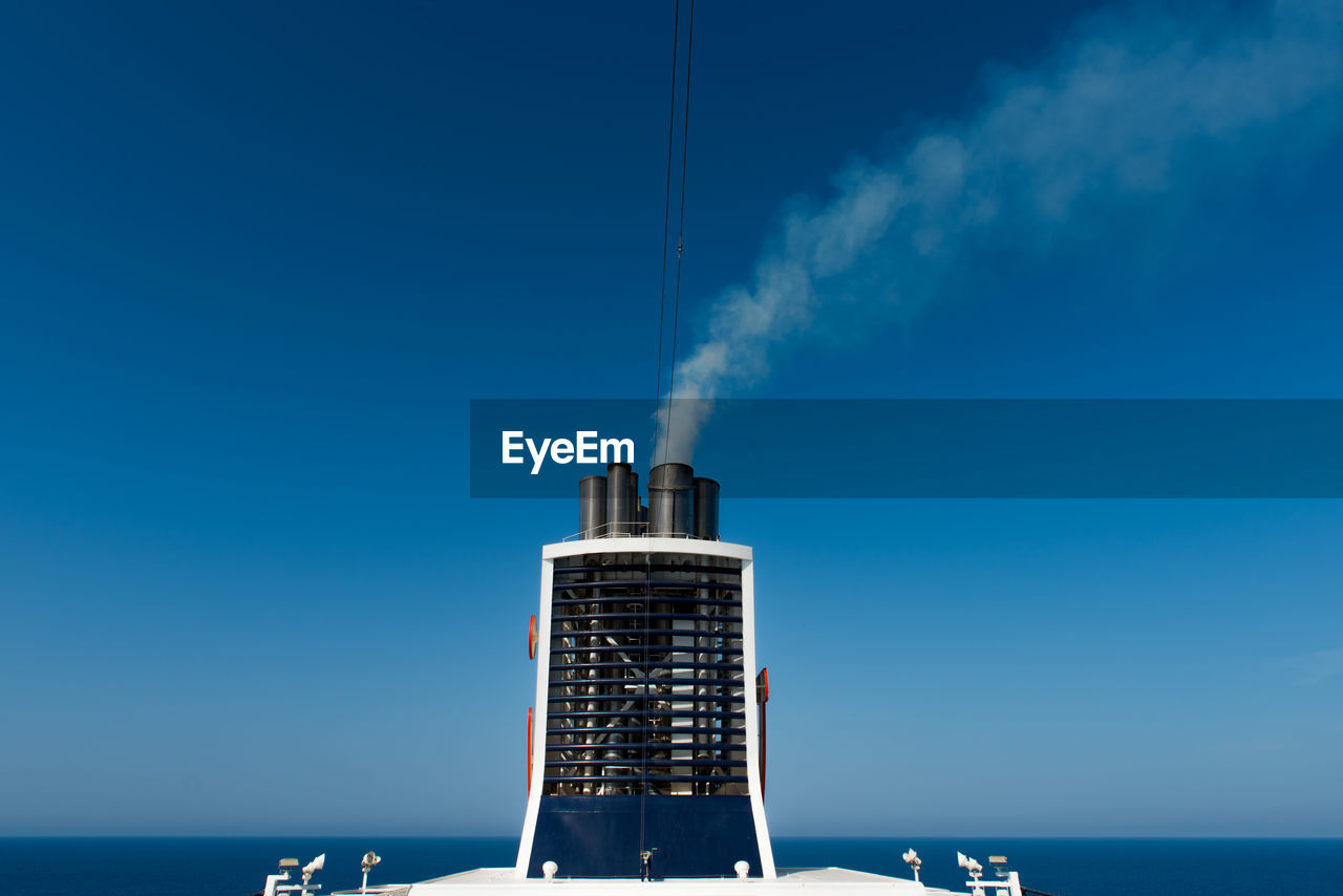 Smoke stack by sea against clear blue sky