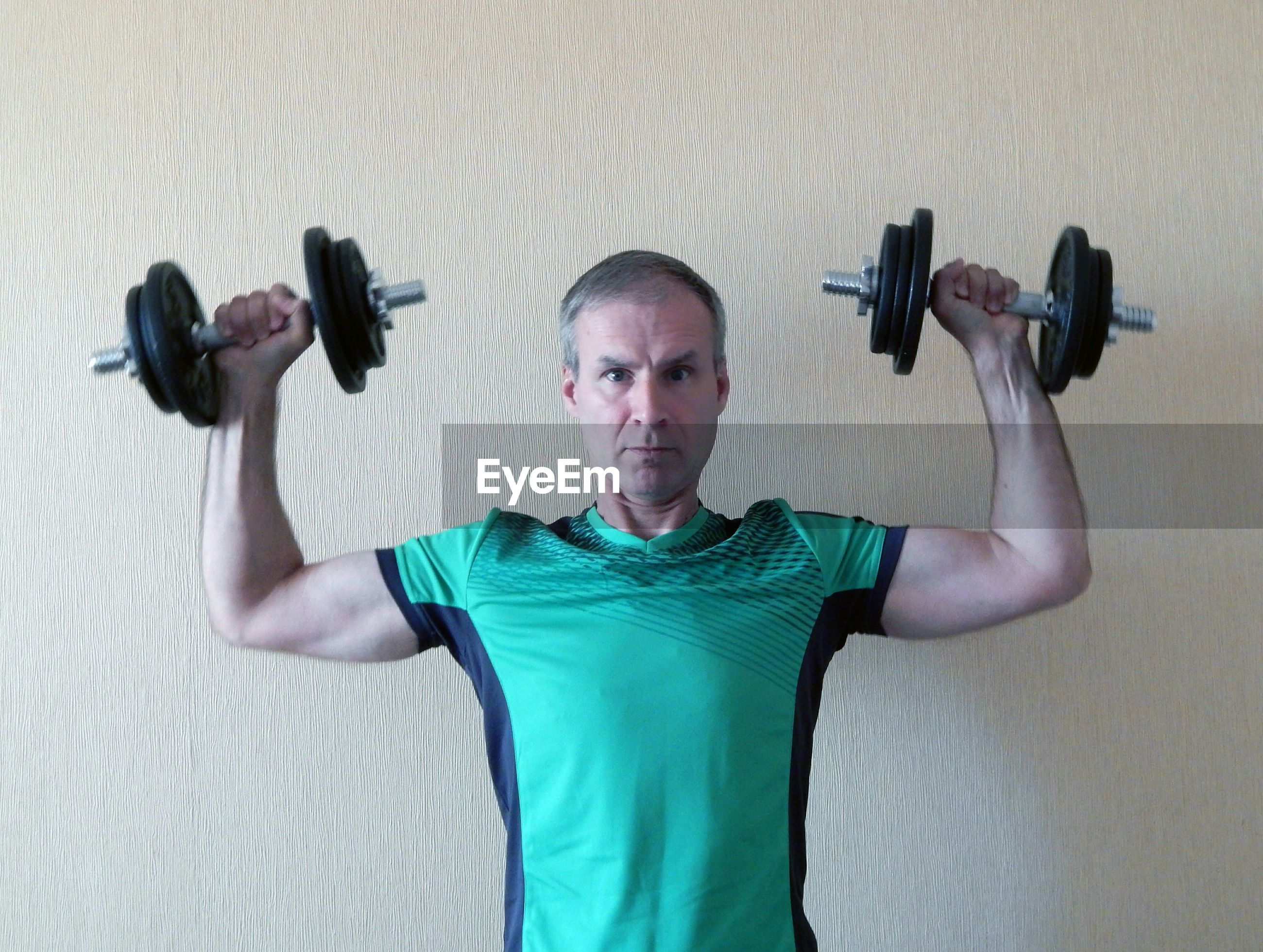 Portrait of man lifting dumbbells while standing against wall