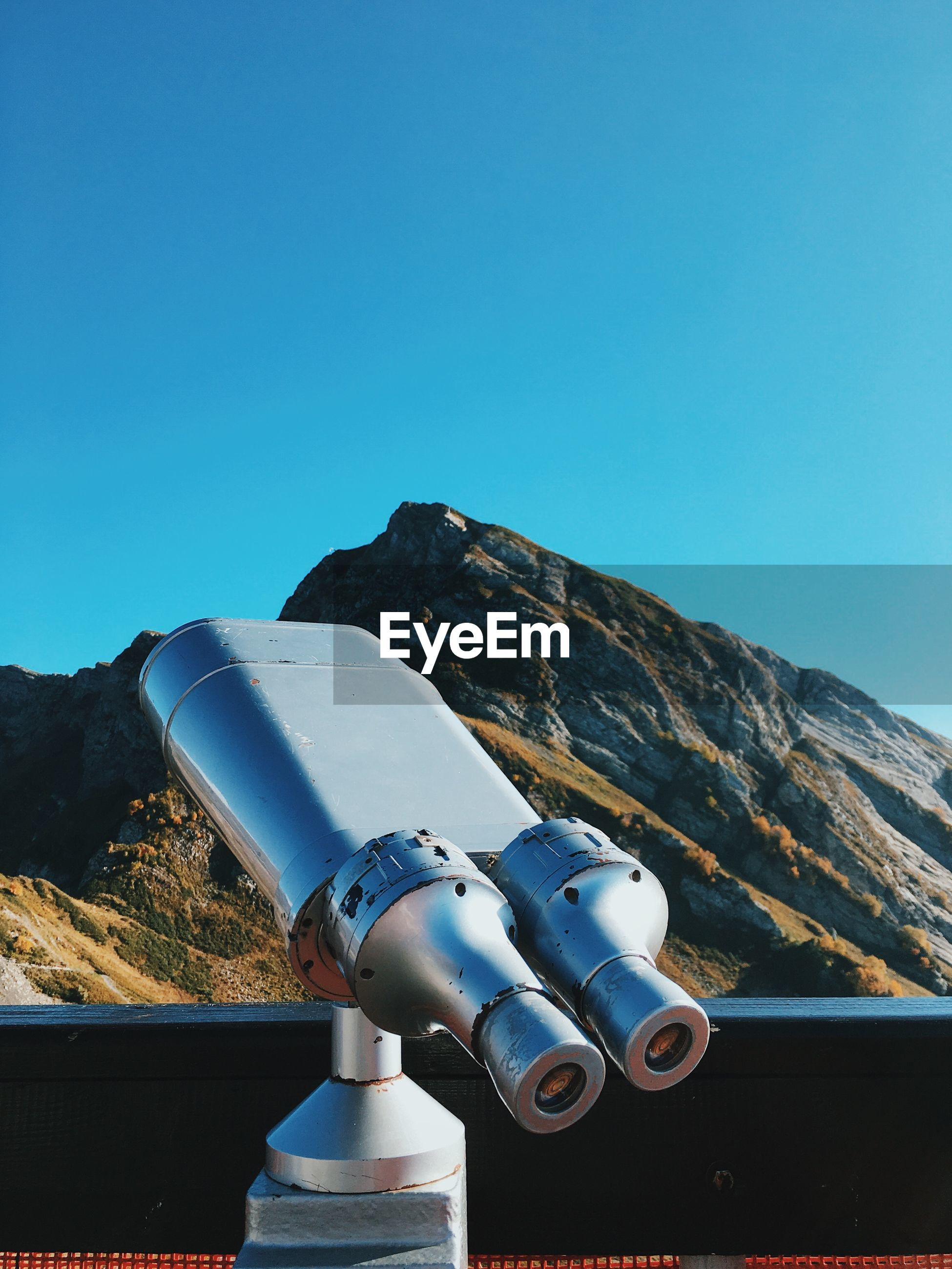 Coin-operated binoculars against clear blue sky