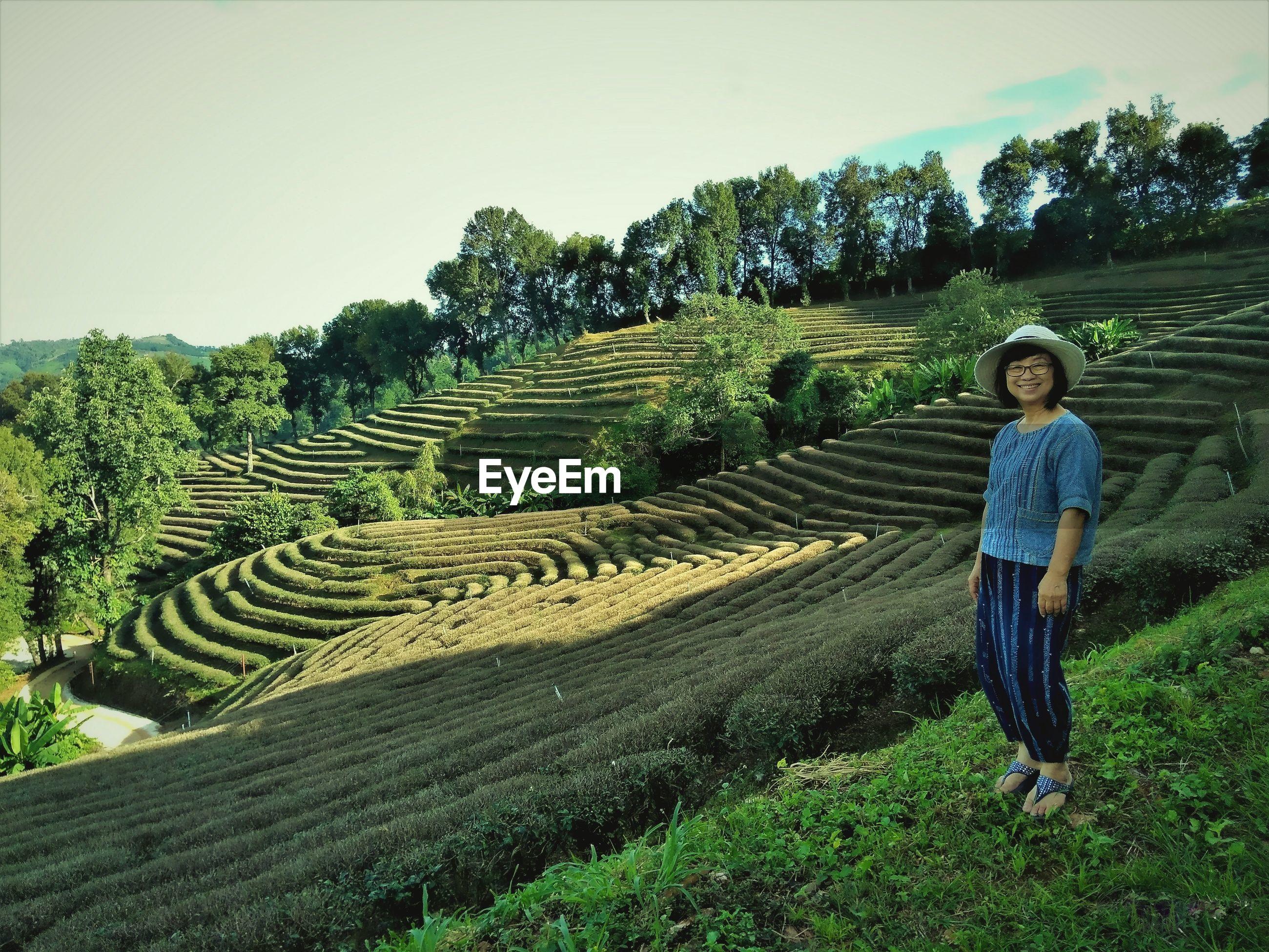 Portrait of woman standing by terraced field