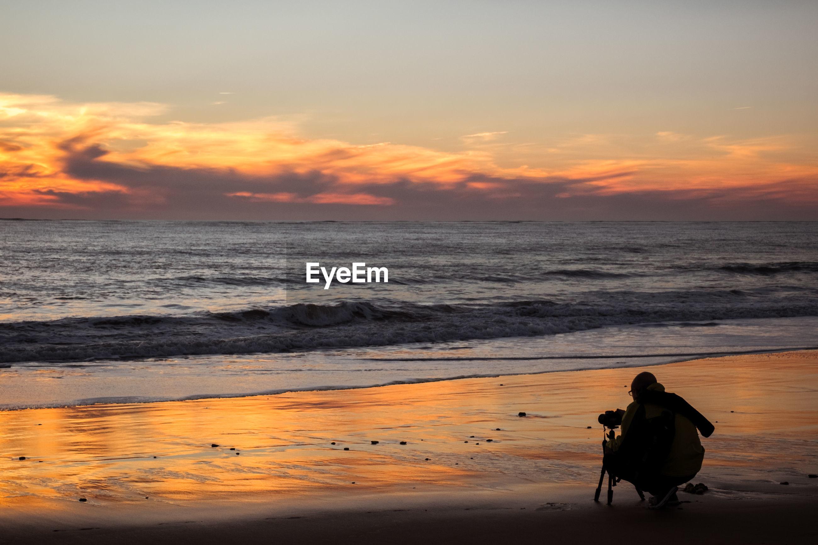 MAN ON BEACH AGAINST SUNSET SKY
