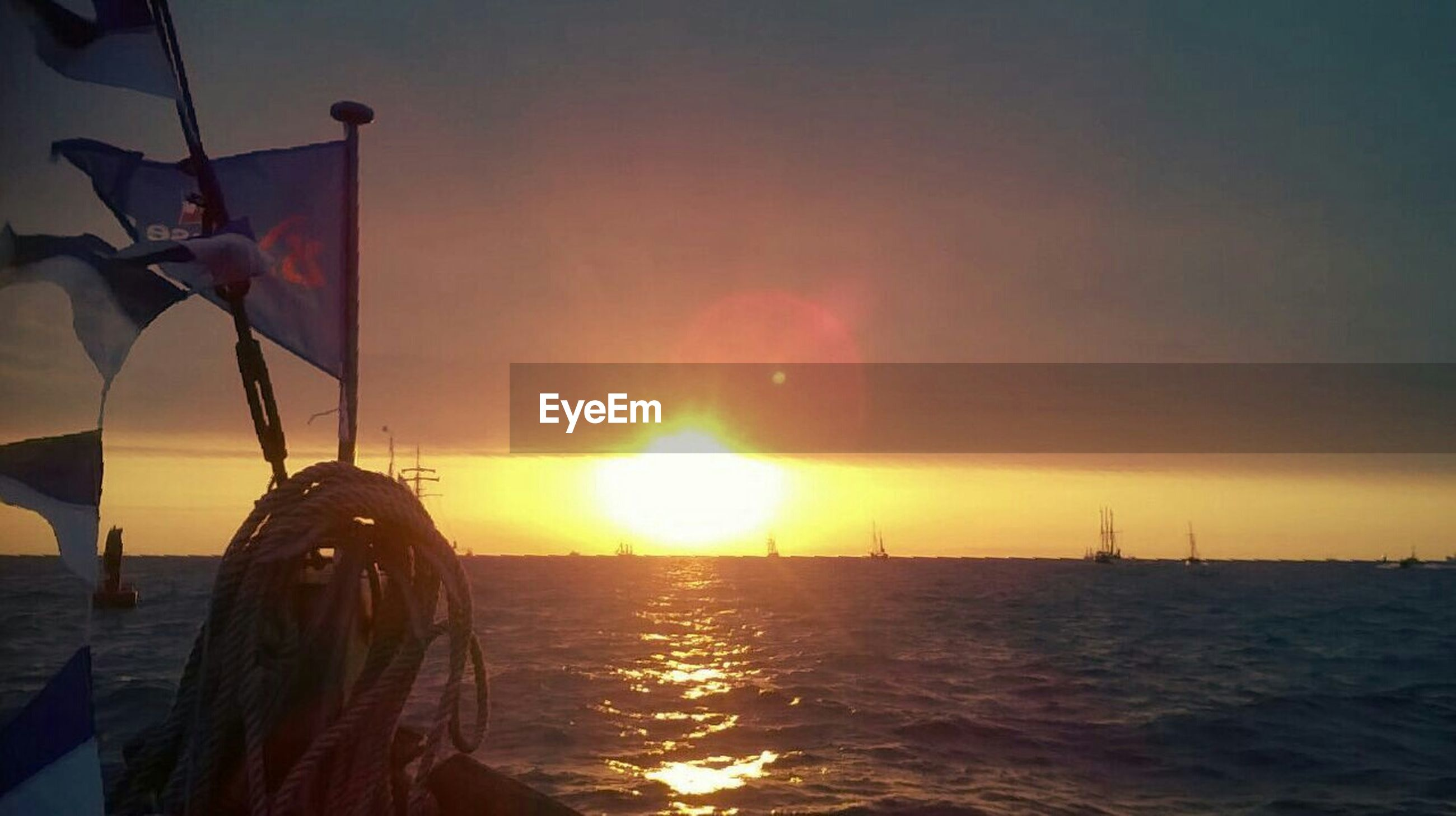 sea, water, sunset, sky, waterfront, sun, nautical vessel, horizon over water, transportation, lifestyles, leisure activity, boat, mode of transport, rippled, sunbeam, nature, scenics, standing