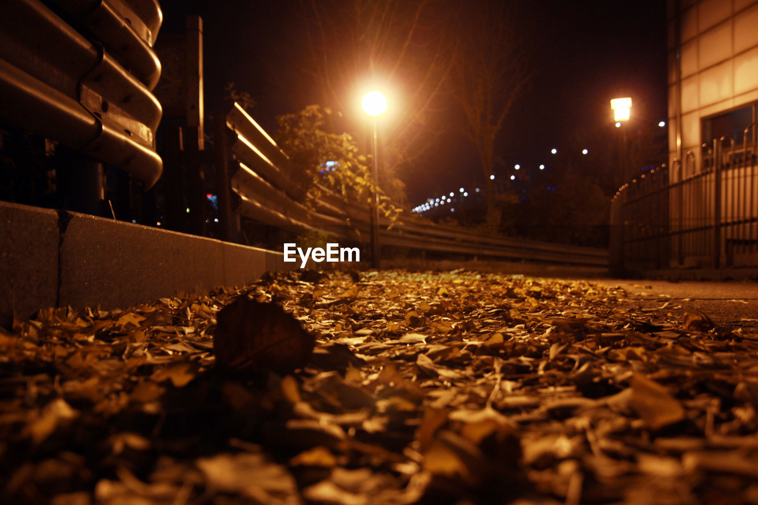 night, illuminated, surface level, railroad track, street light, transportation, the way forward, built structure, lighting equipment, architecture, diminishing perspective, rail transportation, building exterior, street, outdoors, vanishing point, city, connection, no people, selective focus