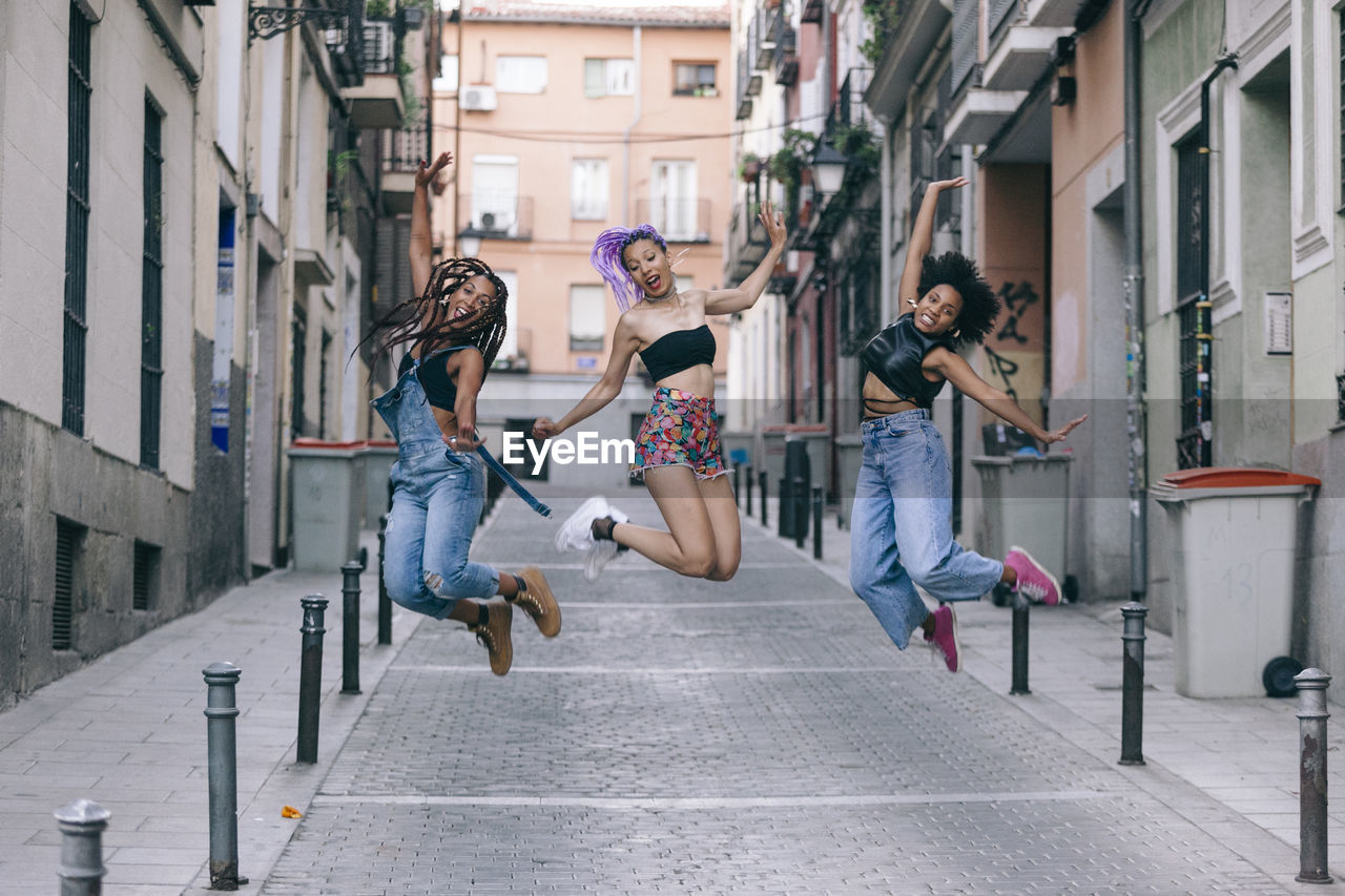 Portrait of friends jumping mid-air in outdoors