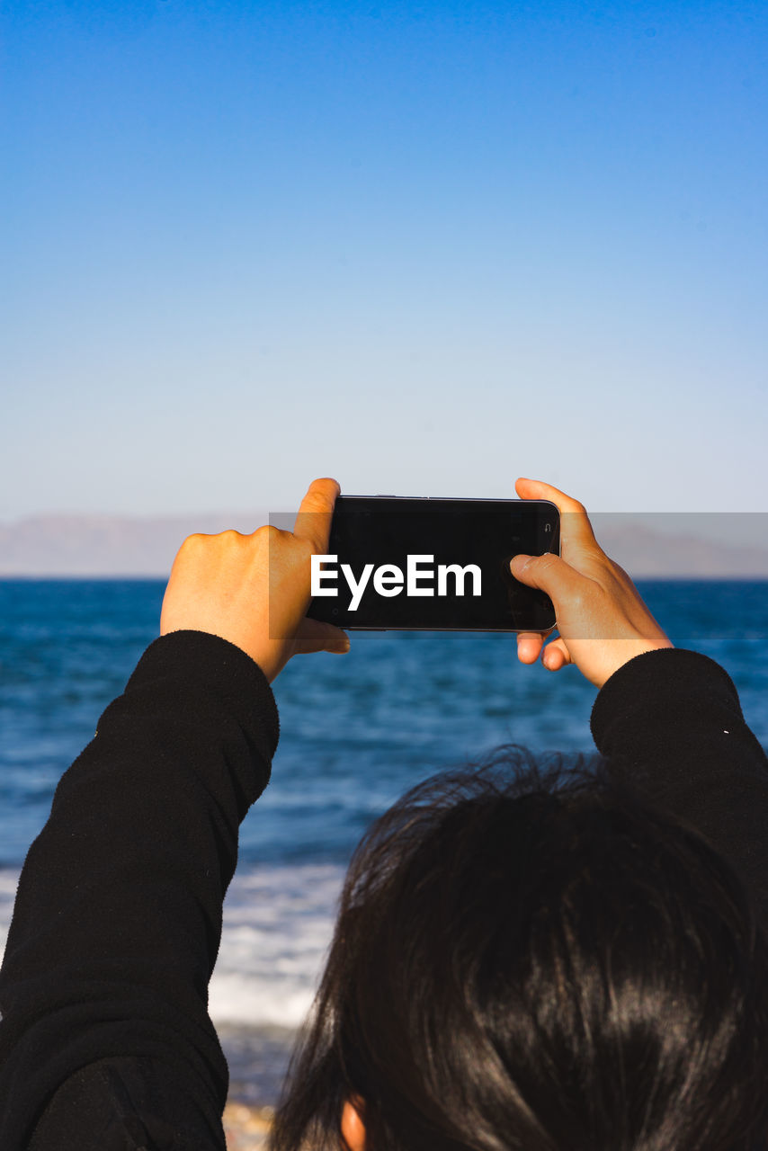 smart phone, wireless technology, mobile phone, water, portable information device, technology, photography themes, sea, sky, nature, communication, lifestyles, photographing, real people, leisure activity, holding, activity, one person, human hand, outdoors, hand