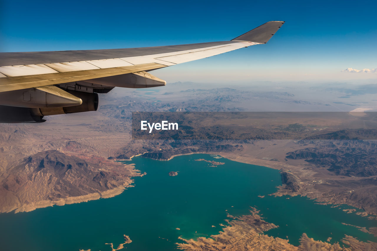air vehicle, airplane, aircraft wing, beauty in nature, scenics - nature, transportation, mode of transportation, aerial view, flying, mountain, nature, water, travel, landscape, mid-air, environment, sky, no people, tranquil scene, snowcapped mountain