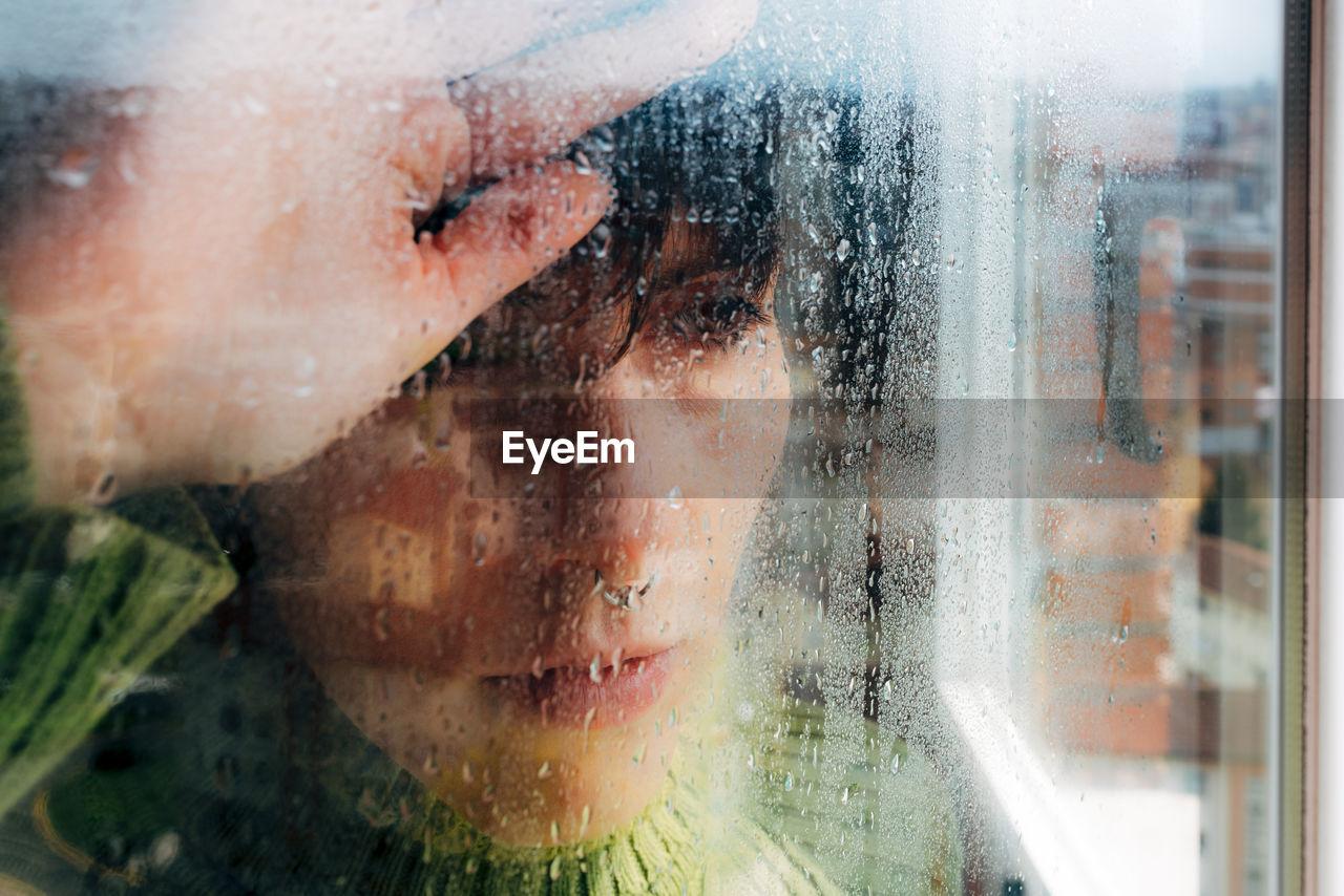 PORTRAIT OF WET BOY LOOKING THROUGH GLASS WINDOW
