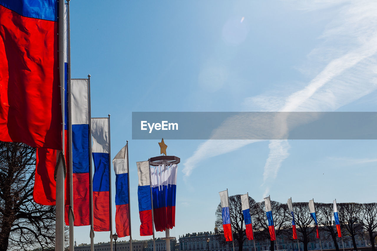 Low angle view of russian flags against sky