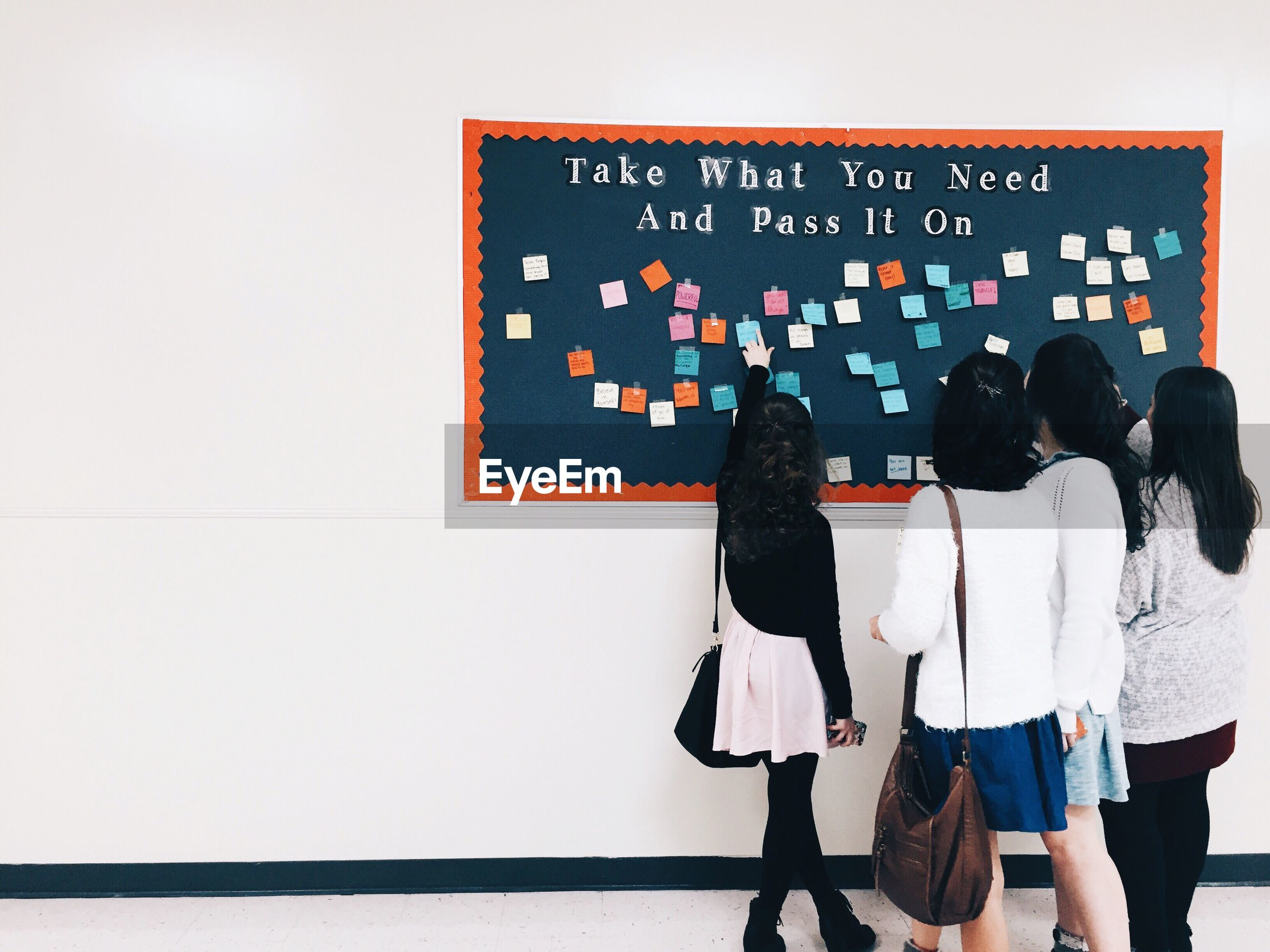 Rear view of students pointing at sticky notes in university corridor