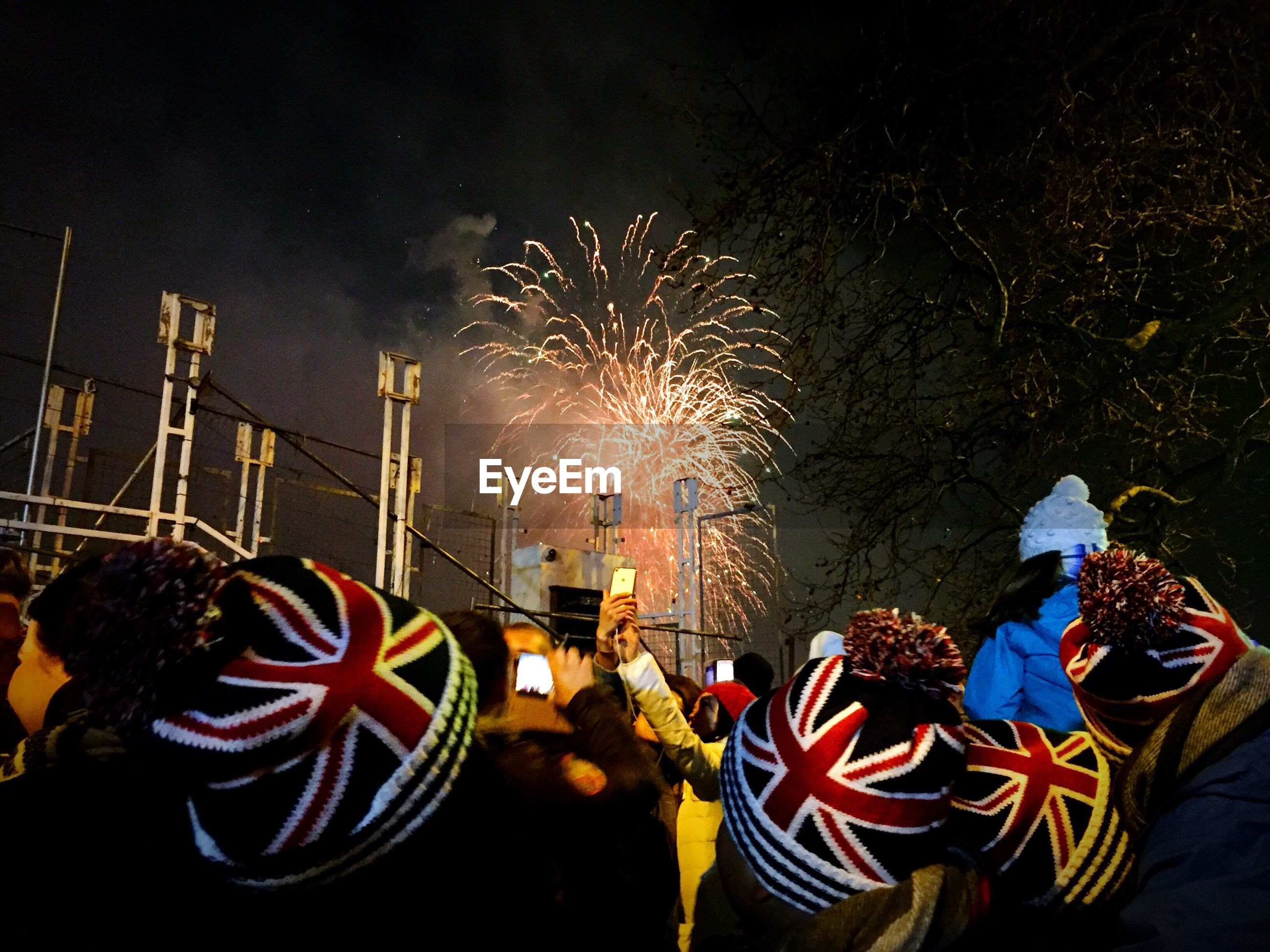 People looking at firework display during night