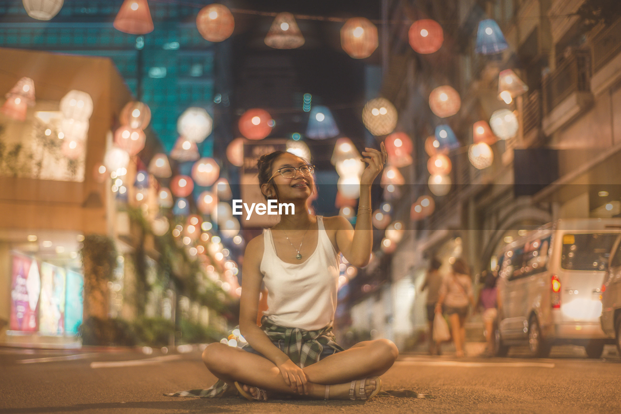 Full length of smiling young woman sitting against decorations on road in city at night