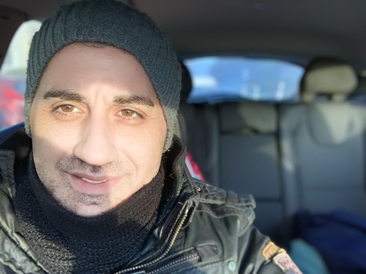 portrait, smiling, one person, mode of transportation, vehicle interior, clothing, transportation, looking at camera, warm clothing, winter, real people, headshot, car, motor vehicle, lifestyles, front view, leisure activity, travel, scarf