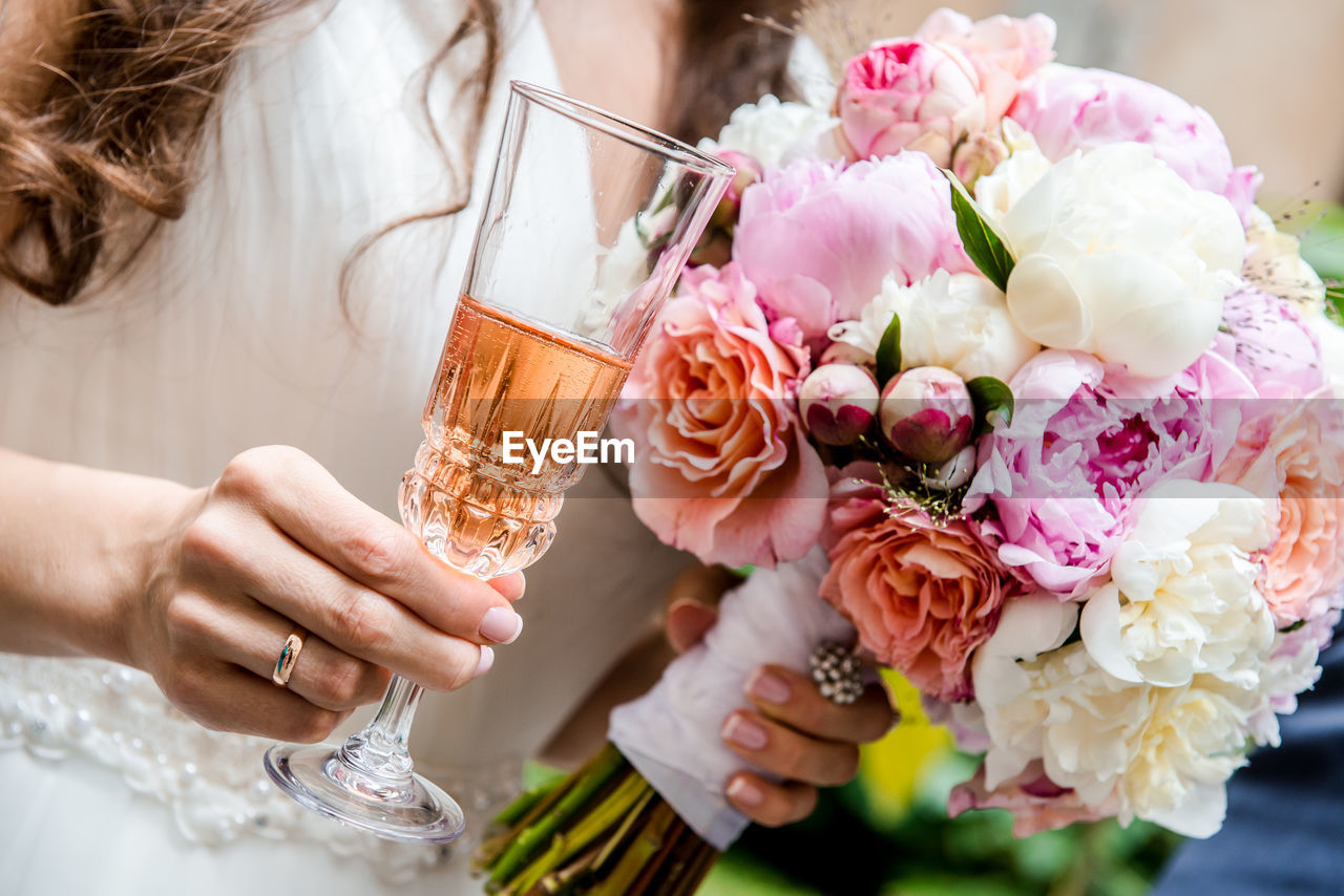Midsection Of Bride With Bouquet Having Drink