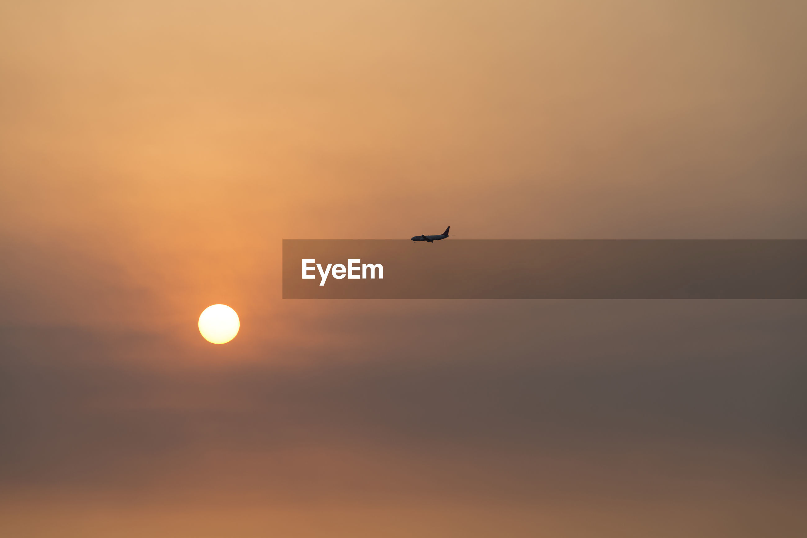 Distant view of airplane flying in sky during sunset