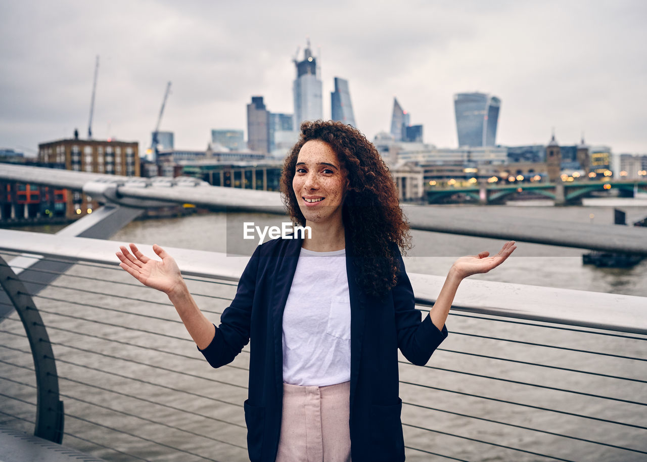 Portrait Of Woman Gesturing While Standing Against Thames River In City