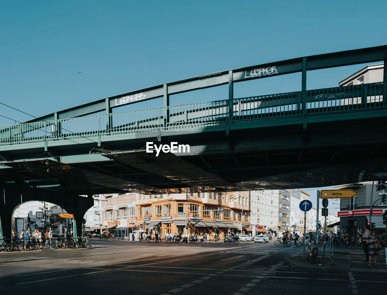 built structure, architecture, transportation, sky, group of people, building exterior, city, bridge, bridge - man made structure, road, incidental people, nature, clear sky, street, connection, mode of transportation, real people, day, public transportation, rail transportation, outdoors