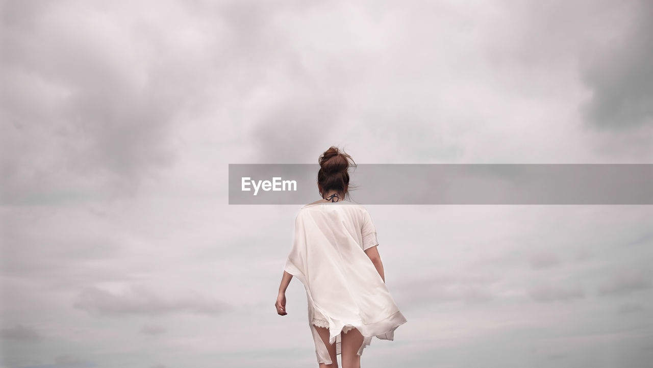 Rear View Of Woman Walking Against Cloudy Sky