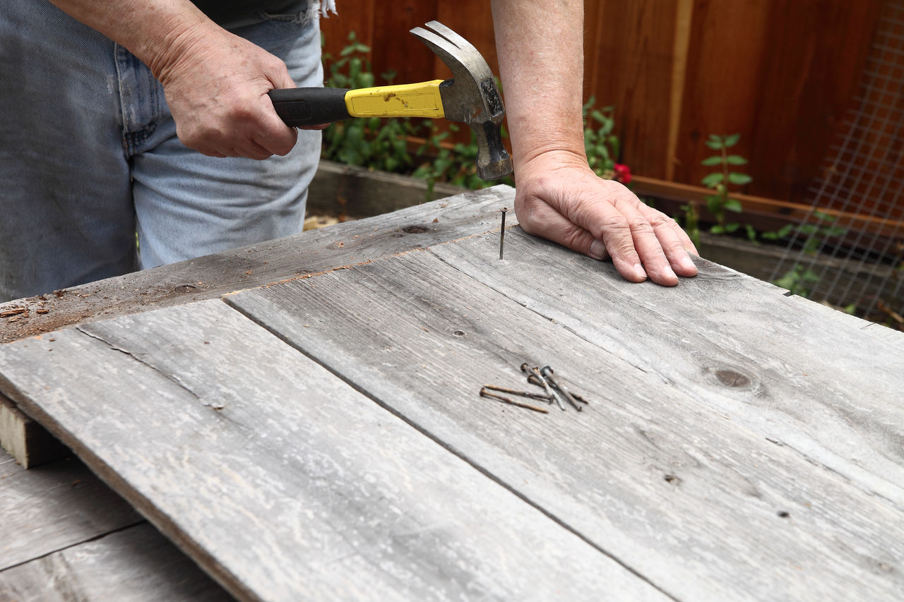 Midsection Of Man Fixing Nail On Wood At Yard
