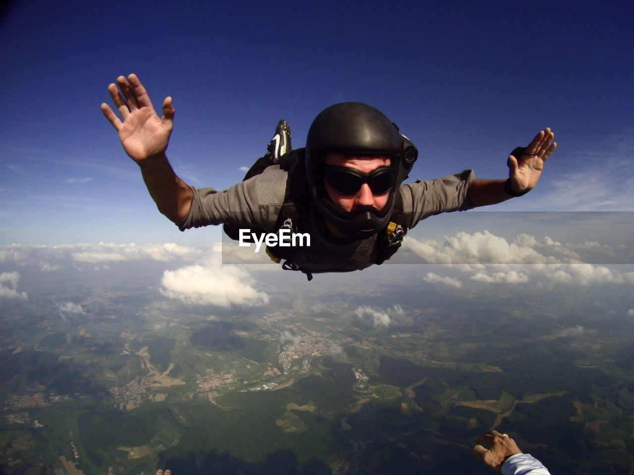 Young Man Skydiving In Mid-Air Against Sky
