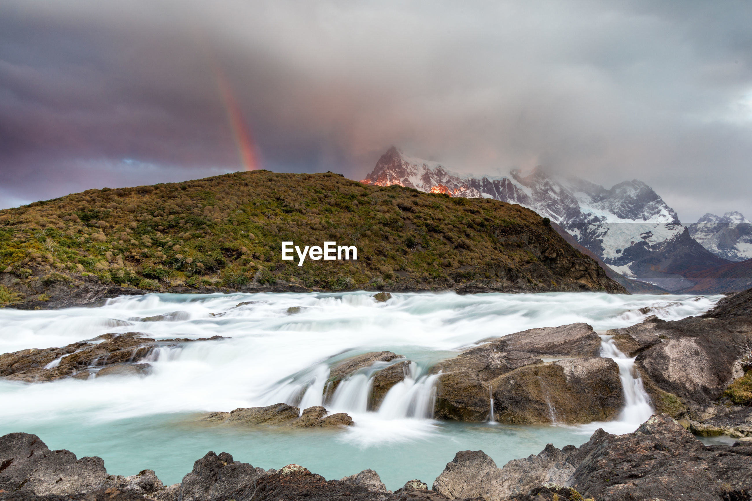Scenic view of river with rainbow over mountain against sky