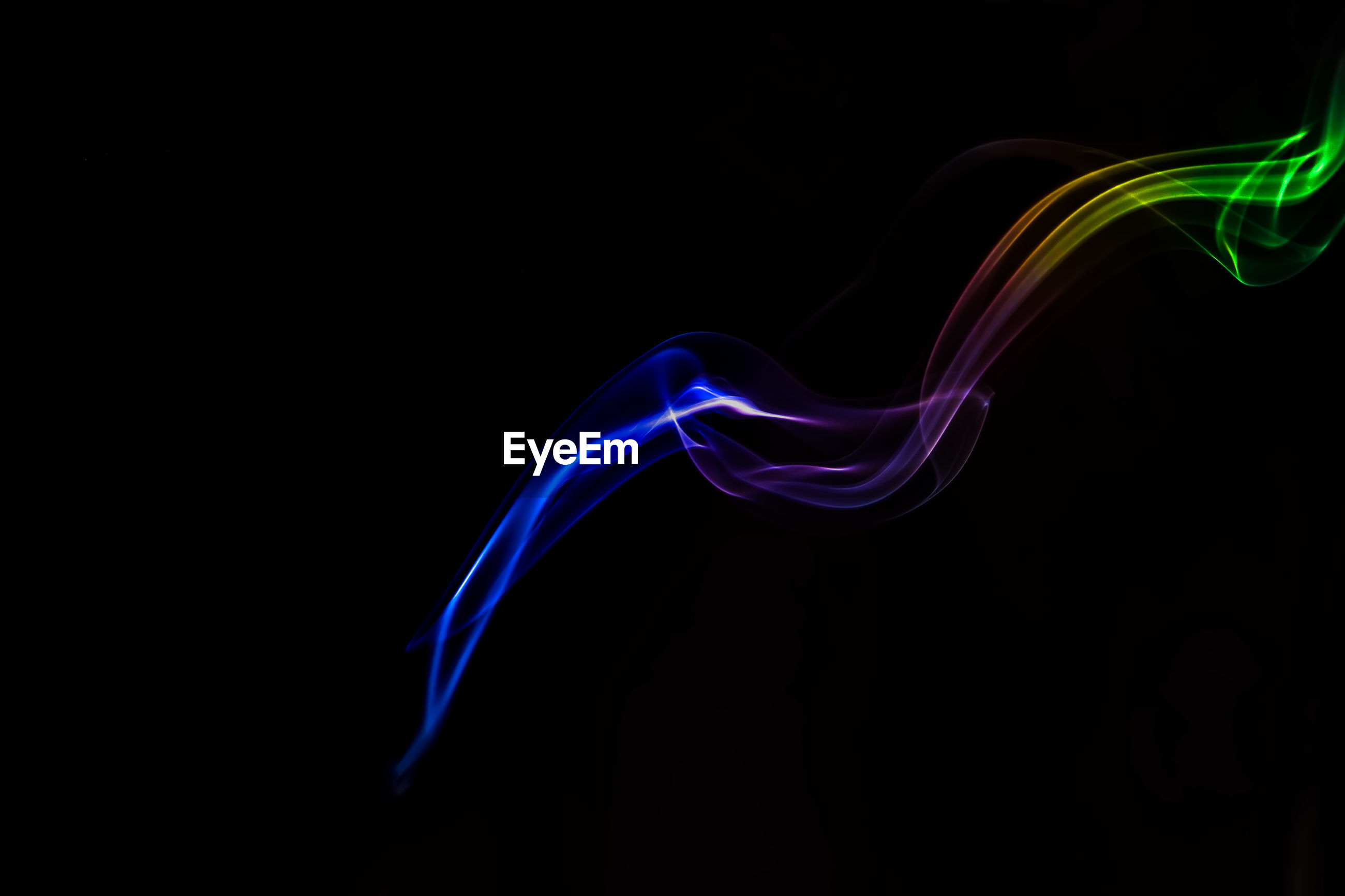 Close-up of multi colored smoke against black background